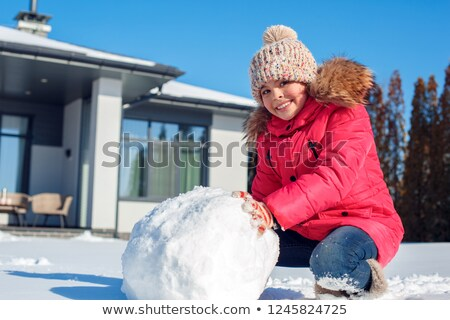 Caucasian woman making a big snowball for snowman. Stock photo © RAStudio