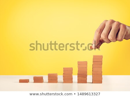 Businessman puts a brick on a bricks pile. Concept of growing statistics and success Stock photo © alphaspirit