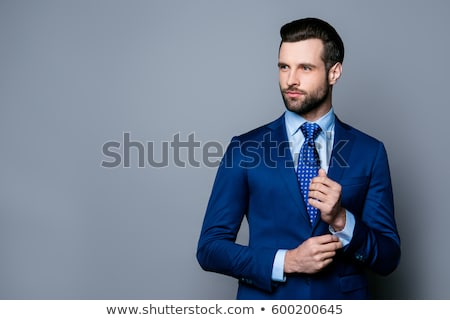 Portrait of joyful handsome man with tied hair and beard smiling Stock photo © deandrobot