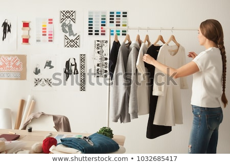 Young female seamstress or fashion designer looking at sketch of new model Stock photo © pressmaster