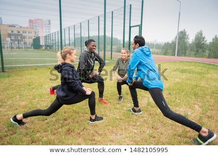 Group of young multicultural friendly people doing stretching exercise for legs Stock photo © pressmaster