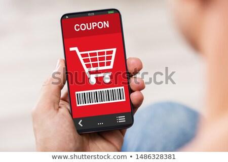 Kéz tart mobiltelefon vásárlás utalvány közelkép Stock fotó © AndreyPopov