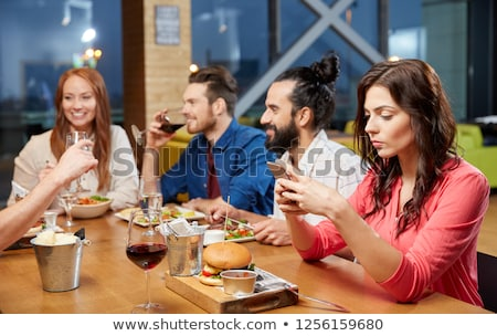 bored woman messaging on smartphone at restaurant Stock photo © dolgachov