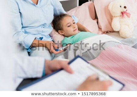 sick little girl lying in bed under blanket while her mother holding thermometer stock photo © pressmaster