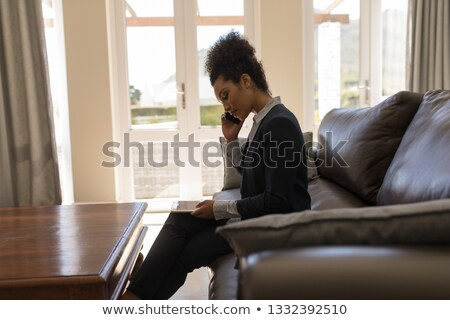 Foto d'archivio: Side View Of A Female African American Real Estate Agent Talking On Mobile Phone While Using Digita