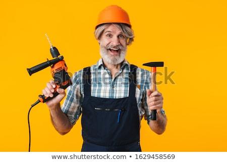 Bearded man builder holding drill. Stock photo © deandrobot