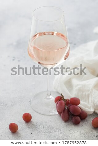 Glass of pink rose wine with grapes and empty glass on light background with linen cloth. Stock photo © DenisMArt