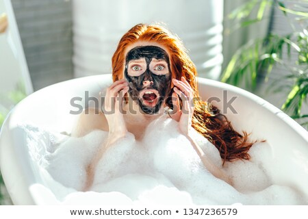 Surprised redhead girl in bathroom. Stock photo © Massonforstock