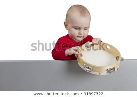 young child holding tambourine behind grey shield stock photo © gewoldi