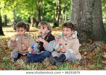 three little girls playing with soap bubble solutions in the forest Stock photo © photography33