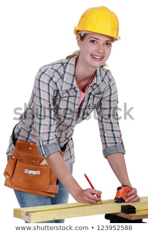 Tradeswoman indicating a measurement on a wooden plank Stock photo © photography33