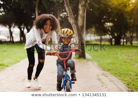 Foto stock: Young Woman Riding Bike In The Park