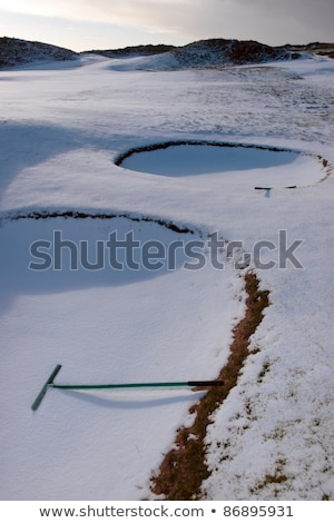 bunker with rake on snow covered links golf course Stock photo © morrbyte