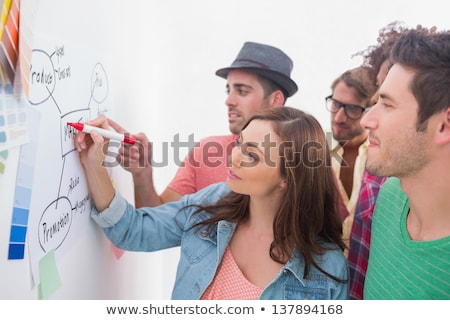 Creative team watching coworker add to flowchart Stock photo © wavebreak_media