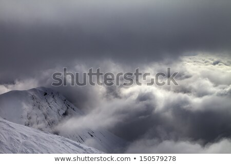 Stock photo: Off-piste slope and snowy rocks in bad weather