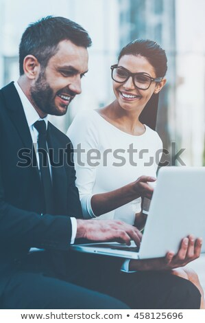 business man works on laptop and looks at you Stock photo © feedough