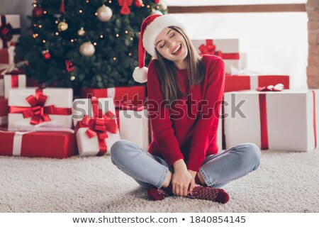Charming woman wearing Santa Claus hat opening Christmas gift Stock photo © HASLOO