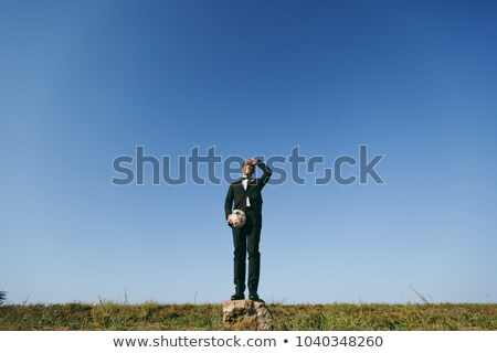 Stock photo: bride stands with the bouquet on to meadow against the background of the sky