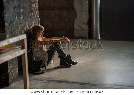 attractive thoughtful female sitting on floor and looking through window stock photo © deandrobot
