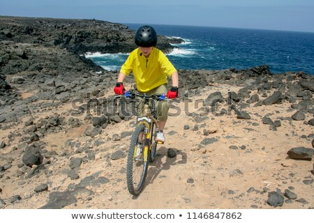 boy riding his mountainbike offroads and doing tricks  Stock photo © meinzahn