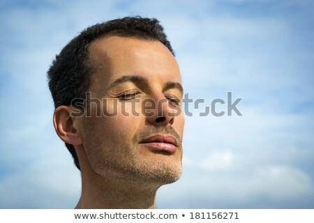 Man with eyes closed meditating on the beach Stock photo © deandrobot