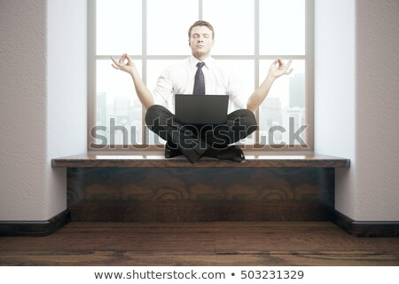 businessman meditating in lotus pose stock photo © rastudio