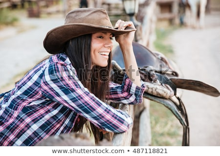 Smiling brunette young woman cowgirl leaning on fence in village Stock photo © deandrobot