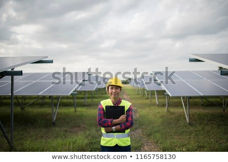 woman checking solar panels and wind turbines stock photo © rastudio
