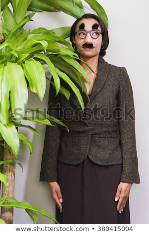 Vertical image of woman hiding behind the plant stock photo © deandrobot