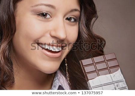 Stok fotoğraf: Cheerful Pretty Young Woman Eating Chocolate Bar And Laughing