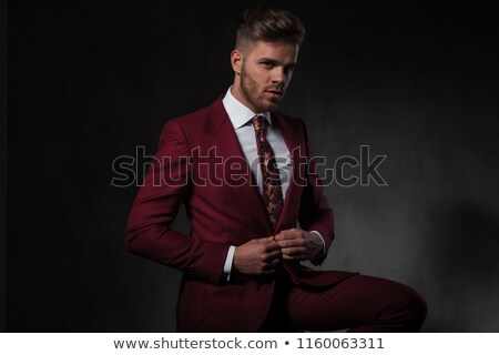 young fashion man sitting on chair closing his coat Stock photo © feedough