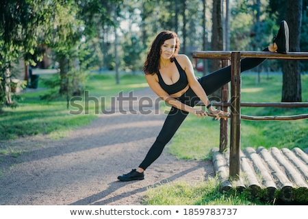 Woman runner stretching against tree Stock photo © IS2