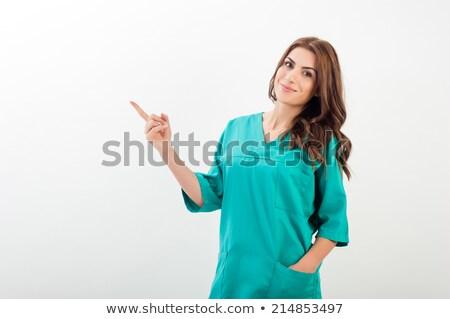 Female doctor pointing up gesture Stock photo © studiostoks
