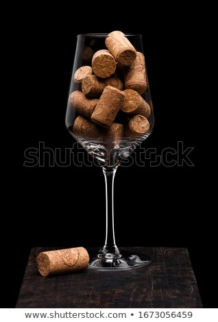 Wine glass with corks inside with cork next to glass on wooden board on black background. Space for  Stock photo © DenisMArt