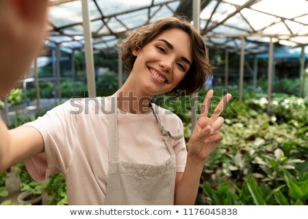 cute woman gardener standing over plants in greenhouse take a selfie by camera with peace gesture stock photo © deandrobot