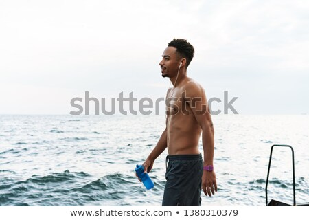 sportsman outdoors at the beach listening music with earphones drinking water stock photo © deandrobot