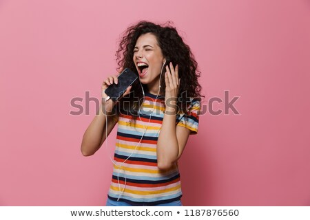 image of cheerful woman 20s with curly hair singing while holdin stock photo © deandrobot
