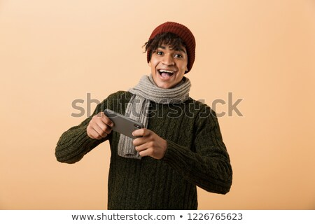 Portrait of young african american guy wearing sweater and scarf Stock photo © deandrobot