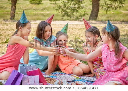 friends clinking drinks at picnic in summer park stock photo © dolgachov