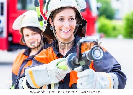 female fire fighters spouting water to extinguish stock photo © kzenon