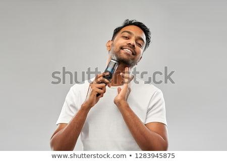 smiling indian man shaving beard with trimmer Stock photo © dolgachov