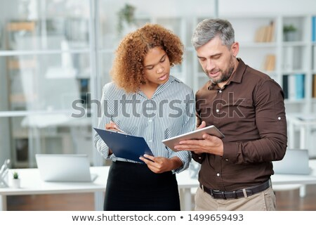 Two contemporary bankers checking financial data on paper and in tablet Stock photo © pressmaster