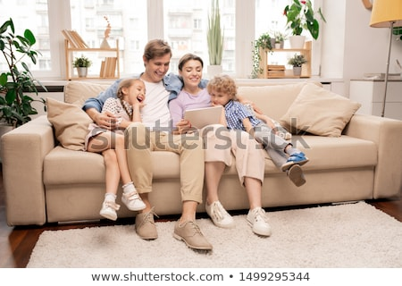 cheerful kids and their parents in casualwear relaxing on couch in living room stock photo © pressmaster