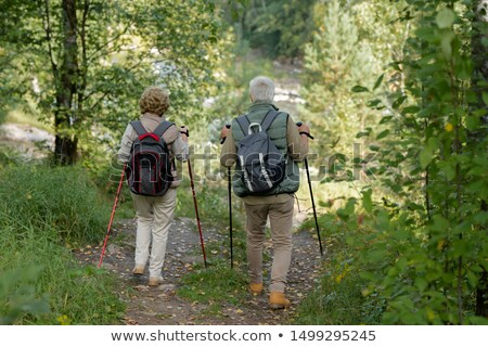 Mature man and woman with trekking sticks moving between green trees and bushes Stock photo © pressmaster
