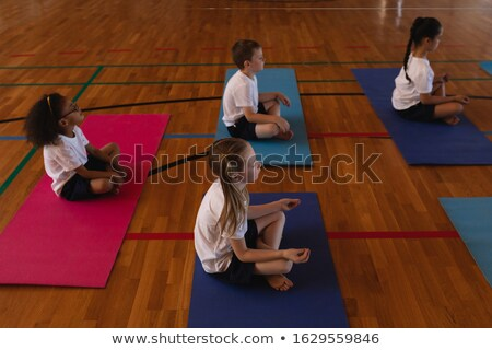 Side view of schoolkids doing yoga and meditating on a yoga mat in school gymnast Stock photo © wavebreak_media