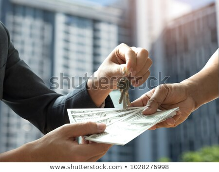 man holding key to the house on background of houses in the city deal with the real estate concept stock photo © galitskaya