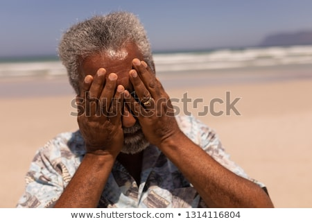 Front view of senior black man with hands on face standing on beach in the sunshine Stock photo © wavebreak_media