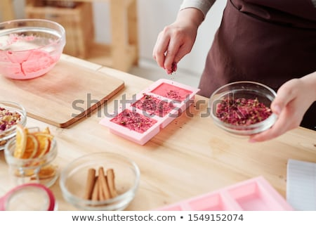 Hands of female sprinkling dry grated floral petals on top of pink soap bars Stock photo © pressmaster