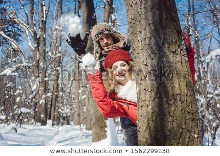 Woman and man in winter throwing snowball hiding behind a tree Stock photo © Kzenon