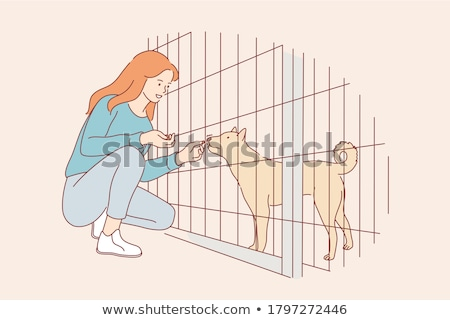 Woman petting a dog in the animal shelter Stock photo © Kzenon